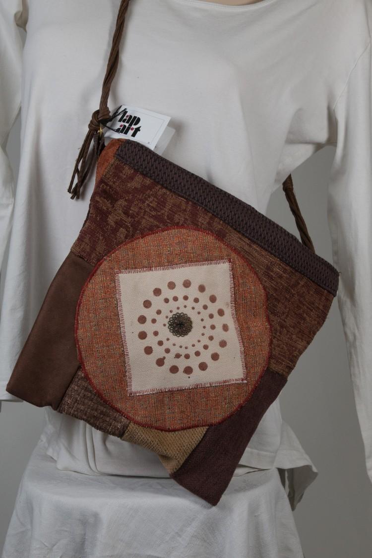 Een tas van resten bekledingsstof met een cirkel en gesjabloneerde versiering